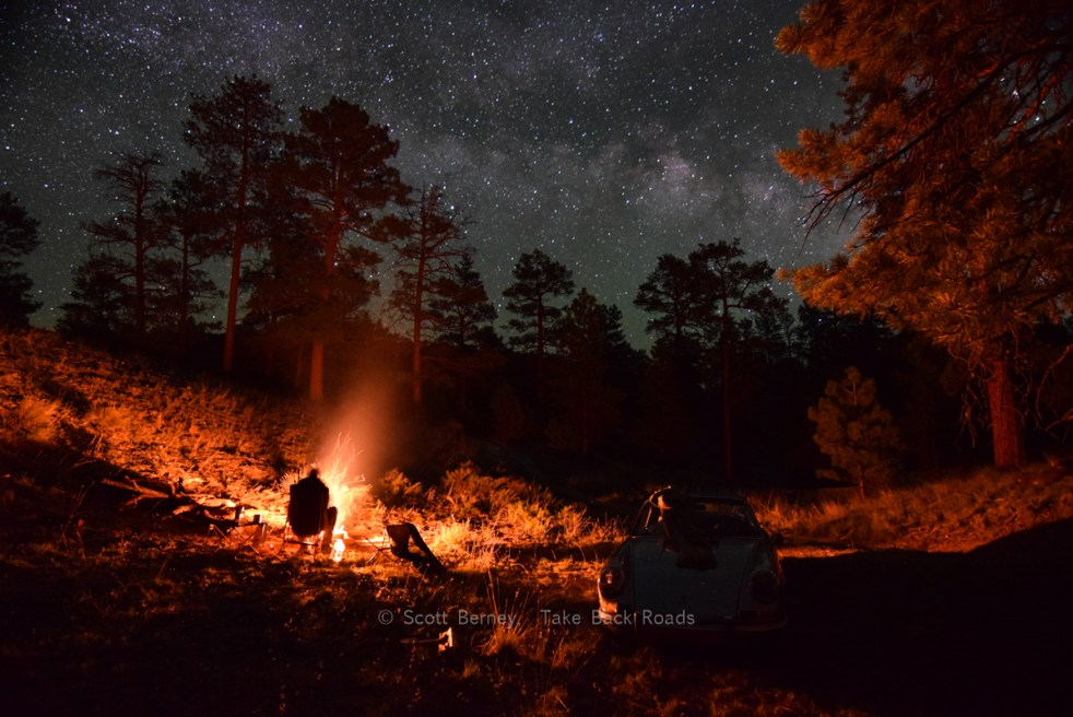 The shadowy silhouette of a camper sits by a campfire in the woods. An antique Porsche 911 sits nearby, under the Milky Way and starry night sky