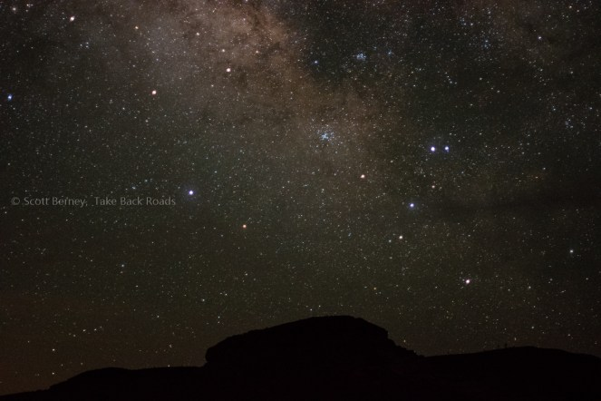 A close up view of the Milky Way and starry sky over the silhouette of a small hill on the horizon.