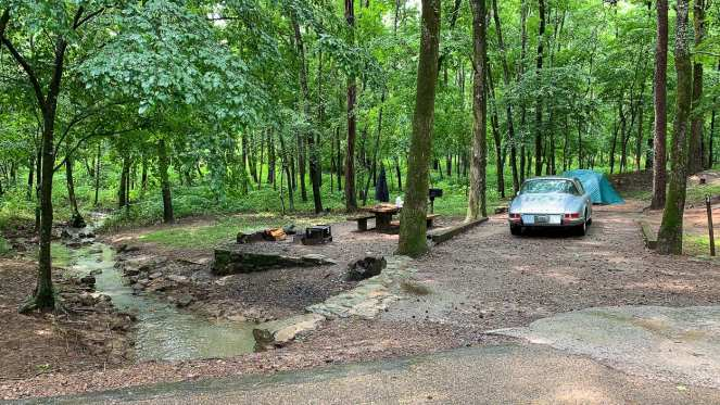 A wooded creekside campground in Ozark National Forest. An antique 1969 Porsche 911 sits in front of a green REI tent. This budget campground enabled us to enjoy our cheap cross country road trip.