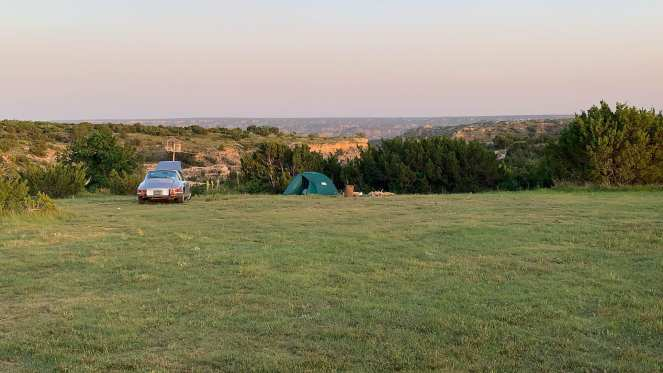 A silver Porsche 911 sits next to a green REI tent pitched near some shrubbery at the edge of Palo Duro Canyon in Texas. This budget campground was a great place to stay during our cheap cross country road trip.