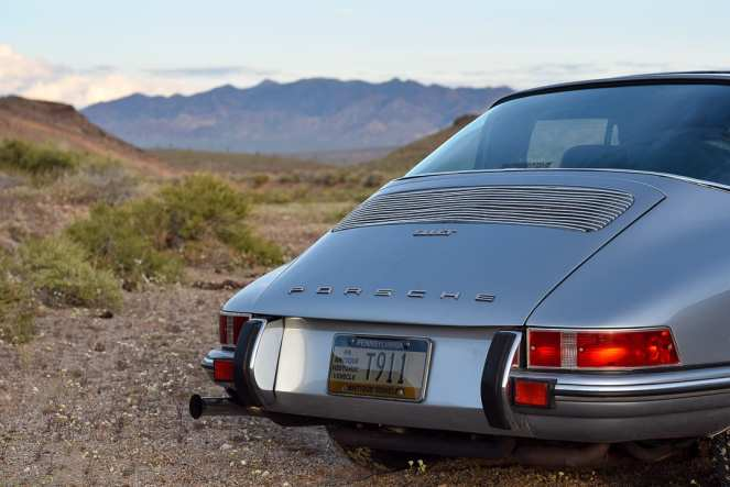 A silver antique Porsche 911 sits in front of the distant jagged mountains on the Nevada horizon, begging the viewer to embark on a cross country road trip