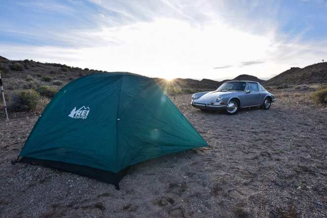 A green REI tent dominates the foreground of a wild desert campsite. A silver Porsche 911 sits in the background, backlit by the setting sun.