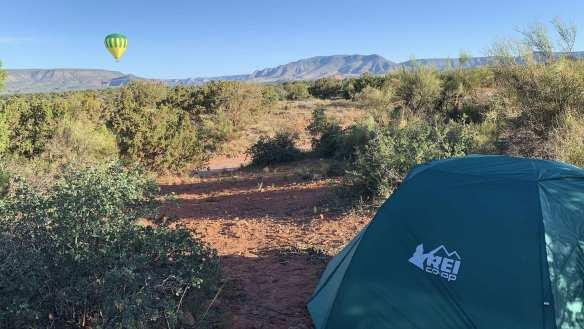 A green REI tent sits on a free campsite in the red dirt of Coconino National Forest near Sedona AZ. A green and yellow hot air balloon floats low along the mountainous horizon. An excellent spot to camp during our cheap cross country road trip.