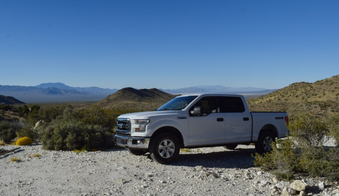 A white Ford F150 crew cab pickup truck sits in the foreground, surrounded by a harsh desert landscape.