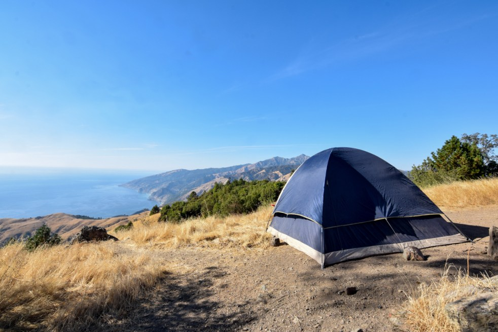 A large blue tent sits on a hill in Big Sur, overlooking the Pacific Coast Highway and the cool blue waters of the Pacific Ocean. A brilliant blue sky overhead is nearly cloudless, and the wild grasses are dried and yellow. This campsite was free.