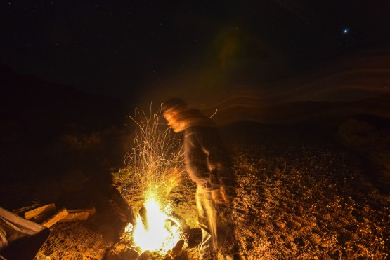 A man prods a small campfire at an isolated wild campsite in the desert, kicking numerous sparks up into the looming darkness