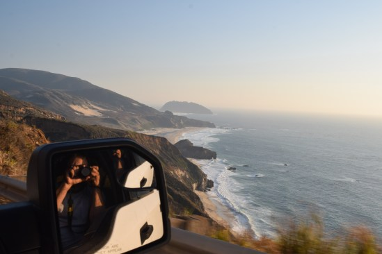 A self-portrait in the sideview mirror of our truck, with the hills of Big Sur California in the hazy background. The foamy waves of the Pacific Ocean crash into the rocky coastline.