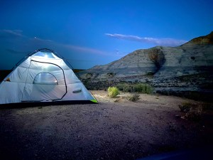 A see through tent sits on the beach at Lone Rock Beach by Lake Powell