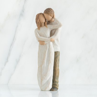 A wooden figurine of a man and woman holding each other