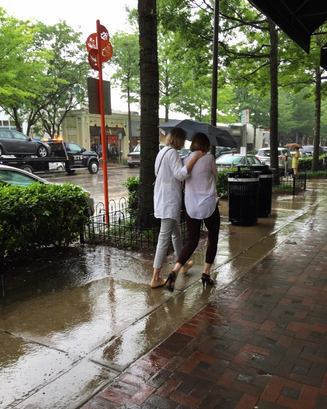 two women under an umbrella during a rain storm in bethesda, maryland