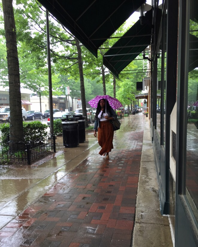 woman with a pink umbrella during a rain storm in bethesda, maryland