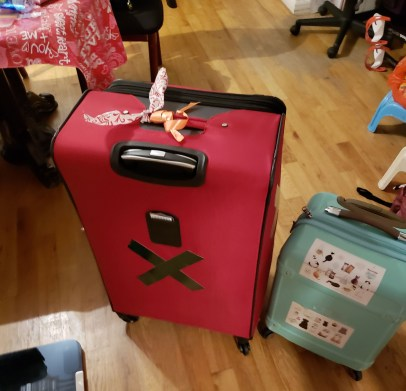 Red luggage with green page and blue luggage with cat stickers