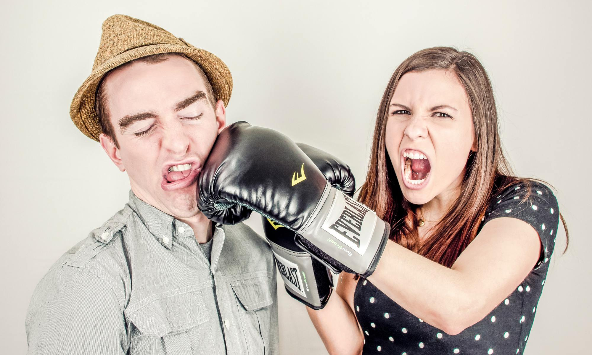 Woman hitting man with boxing gloves