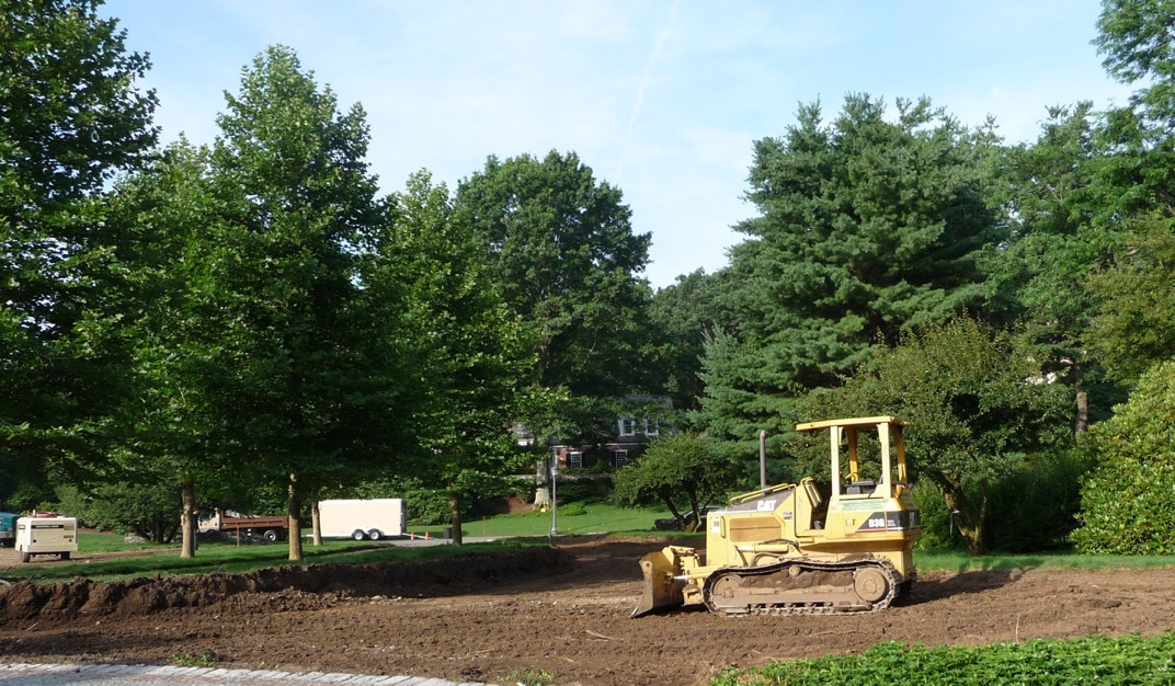 The site before the five London Planes get moved.  The first tree to be excavated and moved is the one furthest from the camera, just to the right of the white trailer.  These trees flanked a driveway; in this photo the driveway asphalt has been taken up and the gravel base has been partially removed.  Trees are located 3-4 feet from the drive edge.