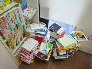 書架が満杯で、床に積み上げられた本