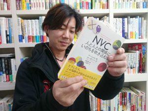 手渡されたNVCの本を眺める和田店長