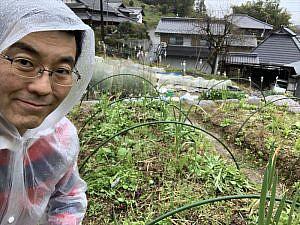 カッパを着て雨の中で農作業