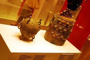 """Dui de bronz - tip de vas antic pentru gatit, decorat cu motivul norului triunghiular, realizat in bronz rosu si argint. Sfarsitul perioadei \""""statelor combatante\"""" - sec. IV - 221 i.Ch. BO de bronz decorat cu dragoni incolaciti - un tip de clopot antic. Sfarsitul perioadei \""""Primaverii si Toamnei\"""", sec VI-476 i.Ch."""