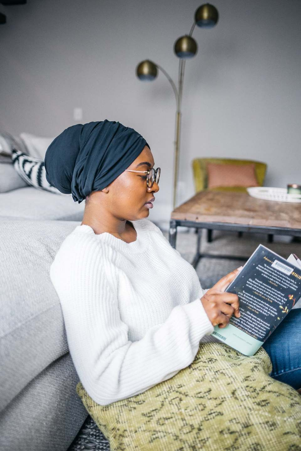 Sitting on a couch reading a book - Self-care