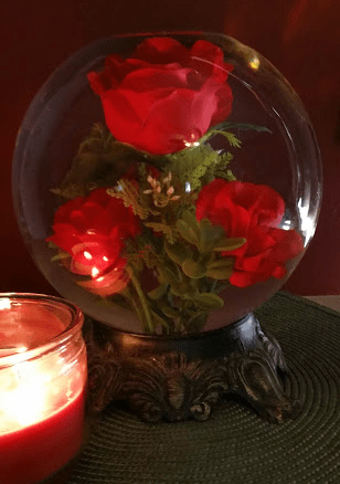 An old water filled rose next to a lit candle. Beautiful in its imperfection.