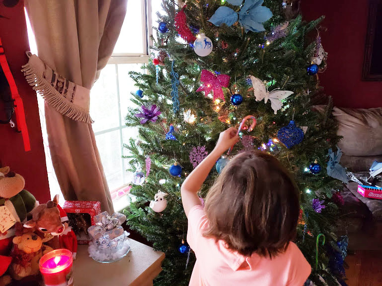 Kids helping to decorate the Cristmas tree based on our family Christmas traditions