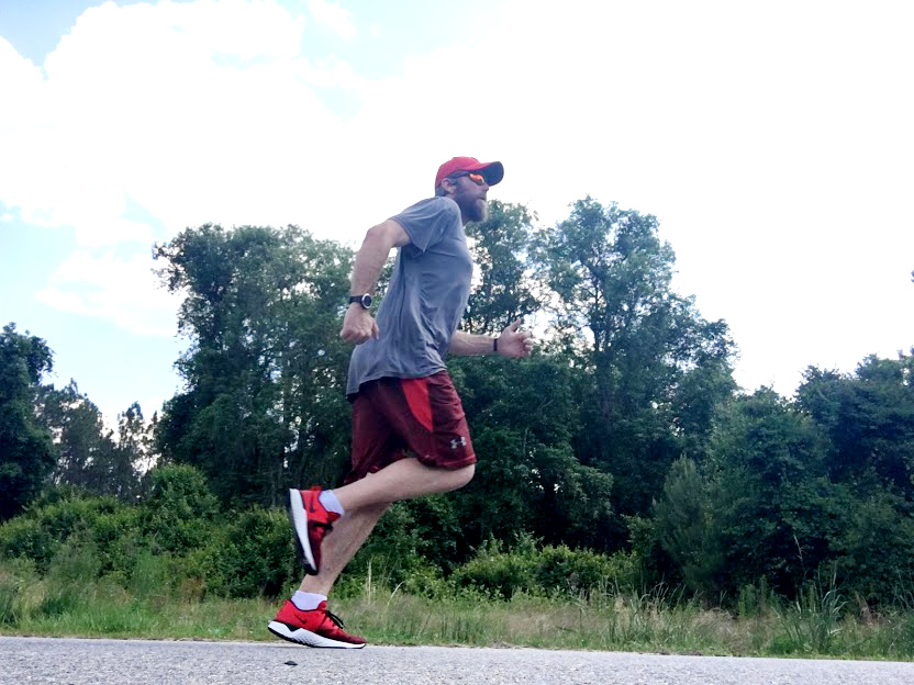 A man doing a speed workout on the road.