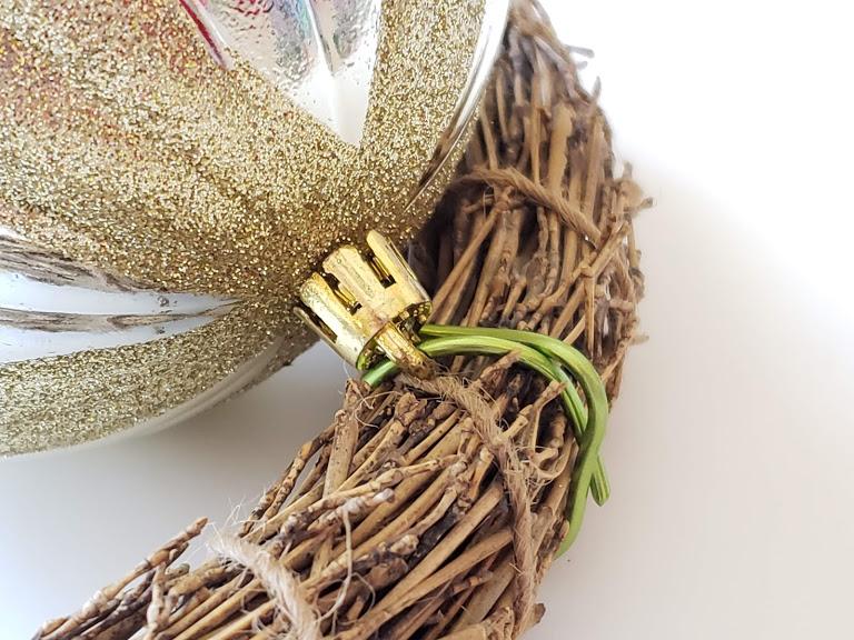 attaching a Christas bulb to a DIY Christmas Wreath