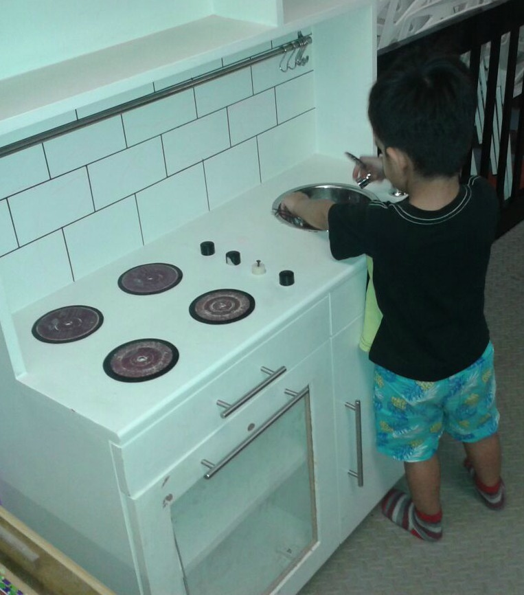 boy playing with kitchen set