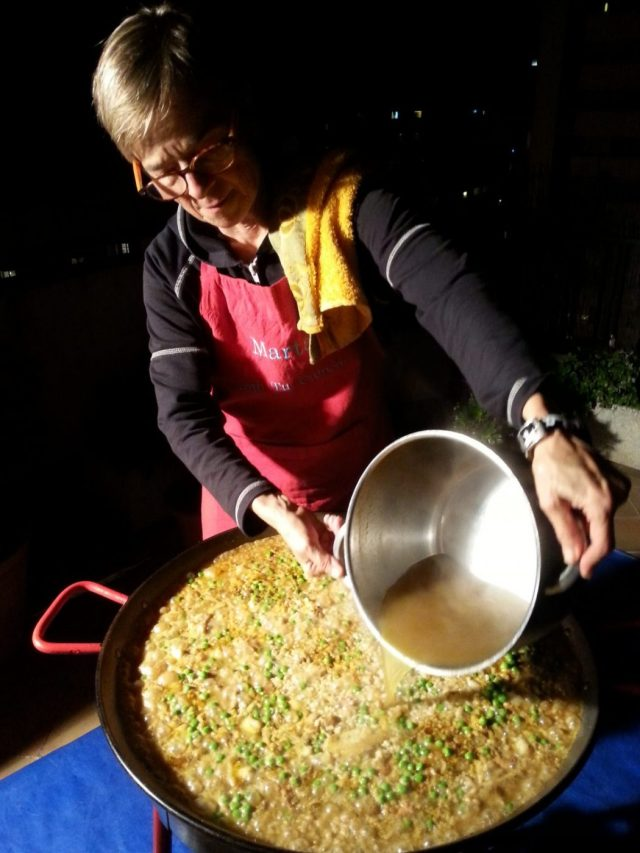 Paella Cooking Class in Barcelona Marta pours in the stock
