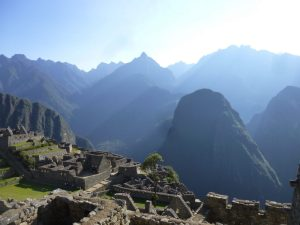 The rays of sunshine peak over the mountains at Machu Picchu