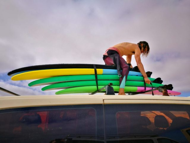 Nando the Surf Instructor tying down our surfboards at the end of the lesson