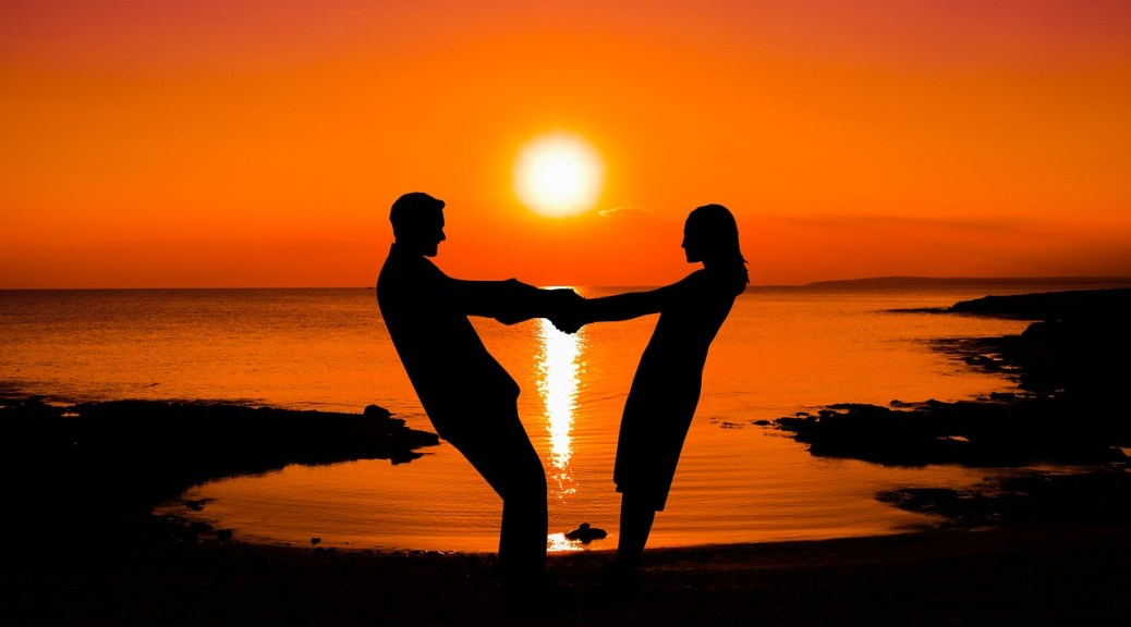 Couple on the beach at sunset - How to Date a Woman who Travels