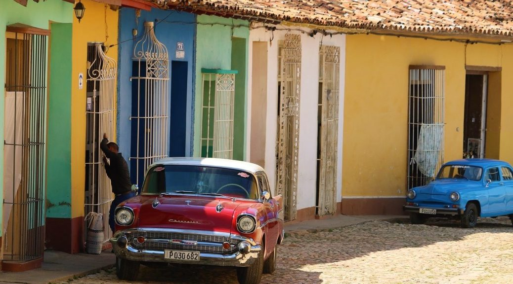 Classic cars outside colourful houses in Cuba