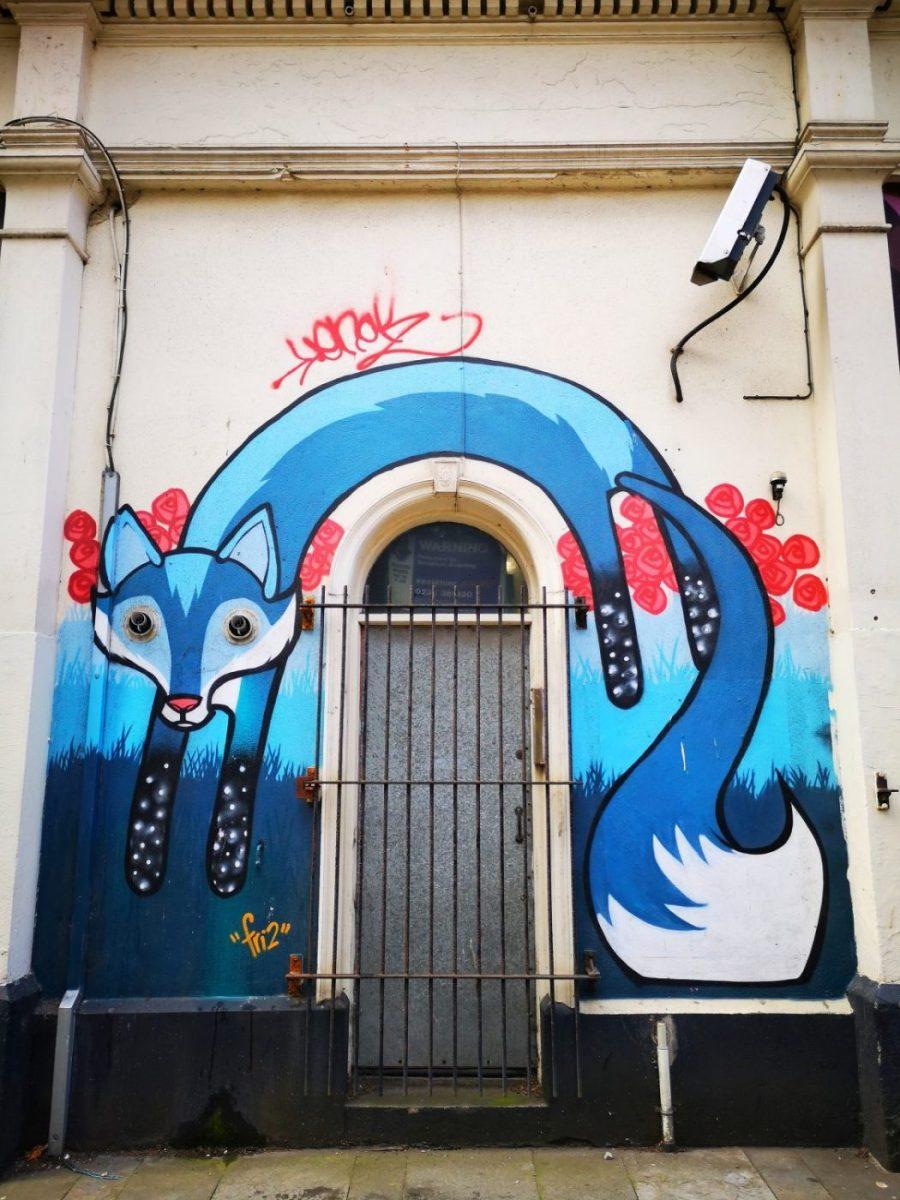 Belfast Street Art - A fox jumping over a doorway