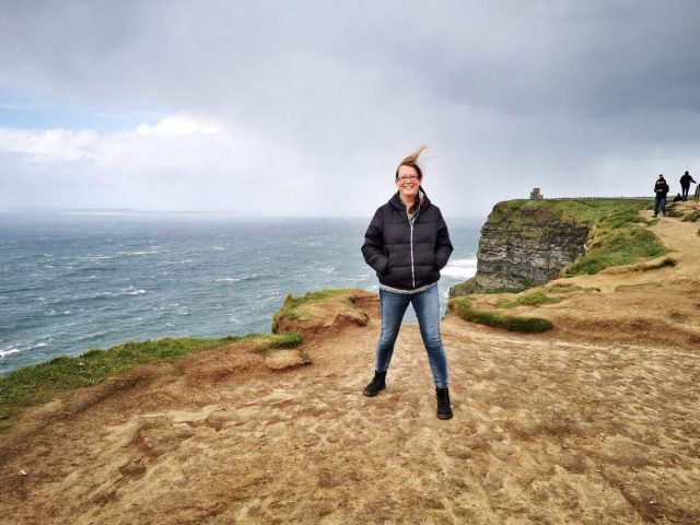 Me trying not to get blown away at the Cliffs of Moher - Visiting the Cliffs of Moher from Galway