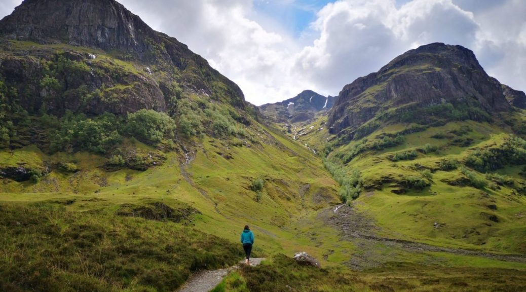 Walking in Glencoe - woman in blue coat walks between epic mountain scenery