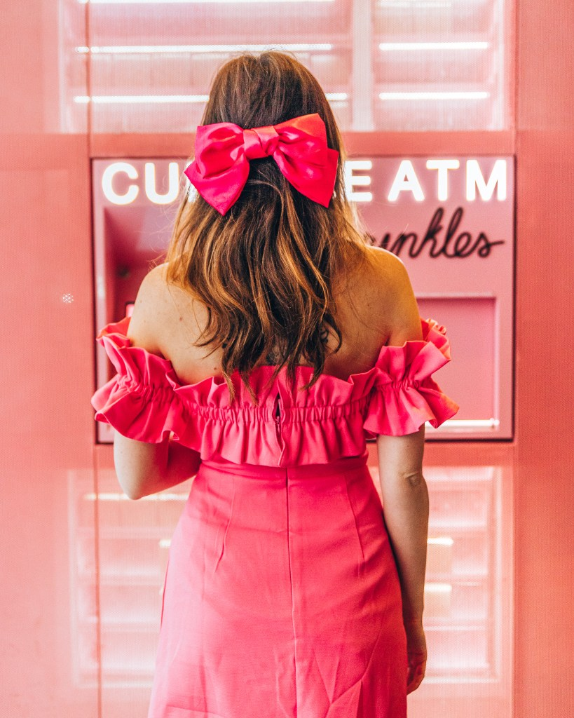 Woman standing with a pink bow in her hair in front of a cupcake atm