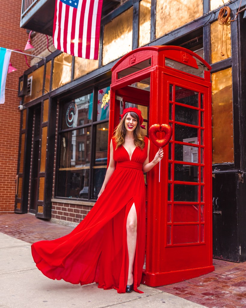 Woman holding a heart balloon in a red dress in front of a phone booth.
