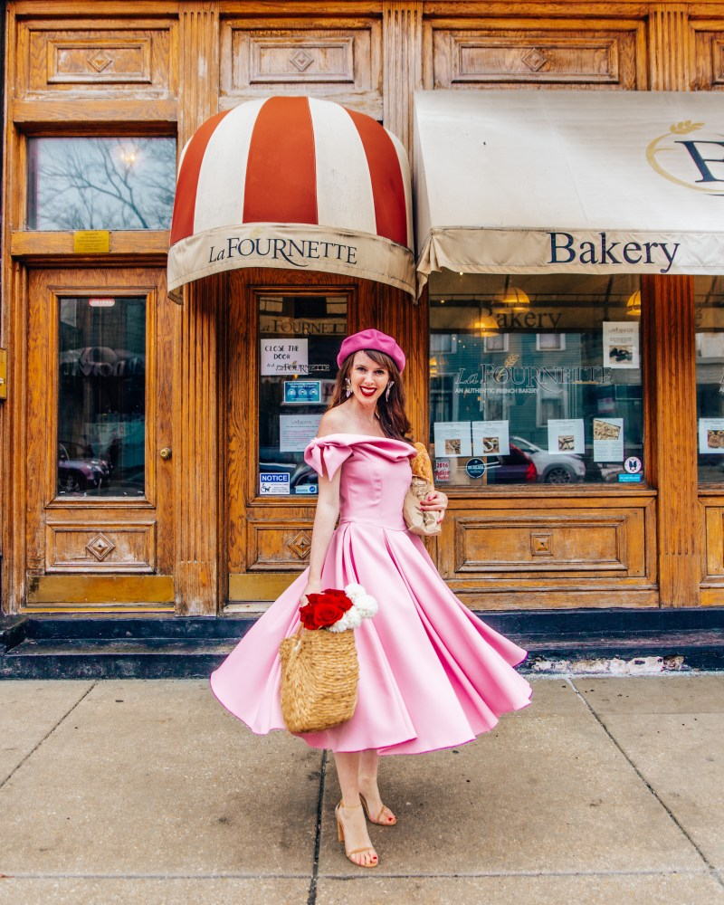 Woman with pink dress and flowers and baguette in front of the bakeryLa fournette bakery