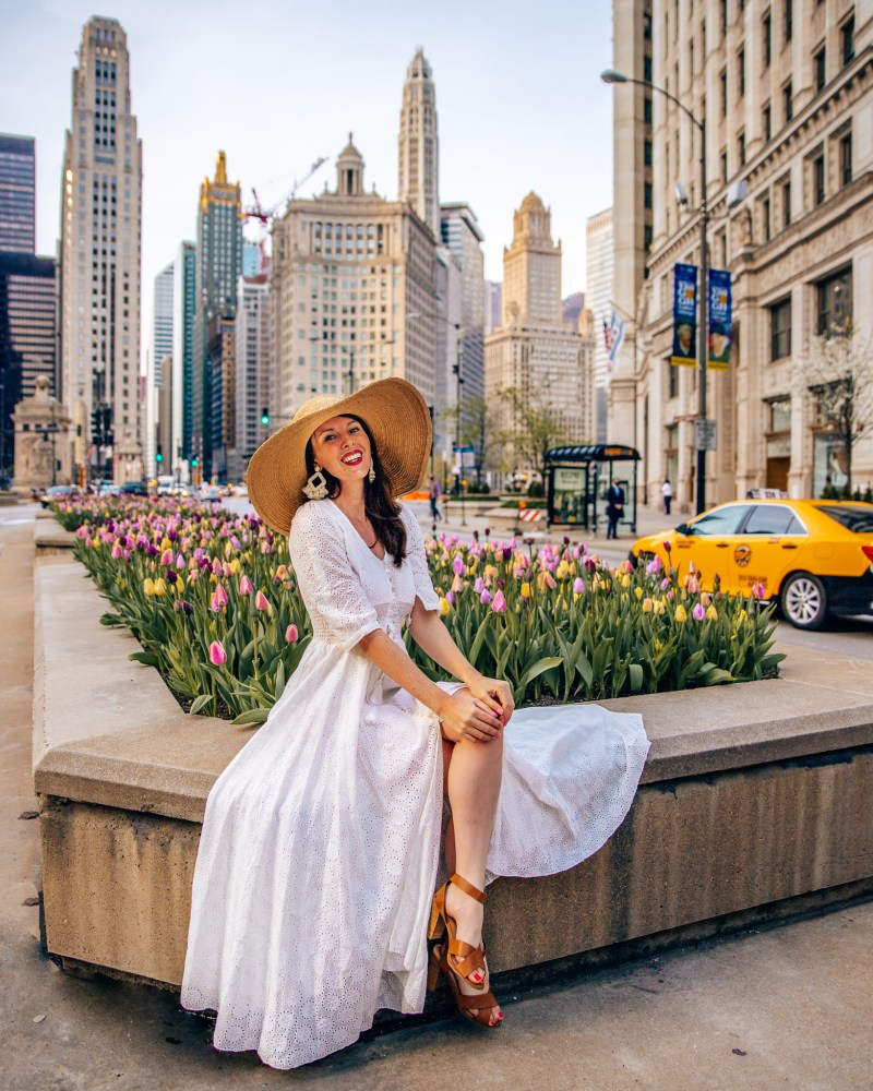 Woman in white dress and hat sitting on tulip island on Michigan Avenue during spring