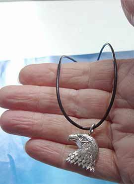 colgante de cabeza de plata en la mano