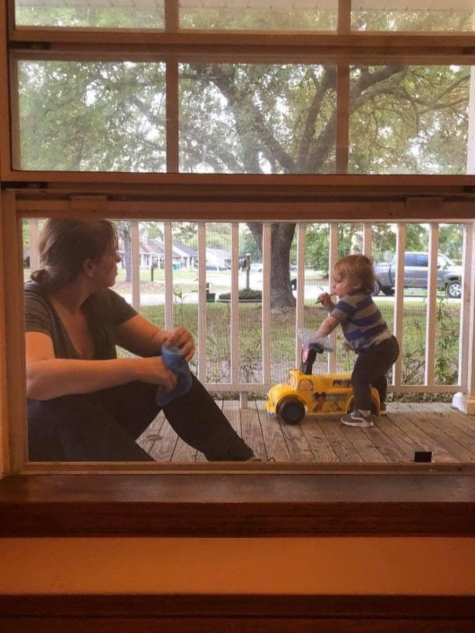 Wednesday, March 18, 2020 – Talking through screened window. He's too little to understand social distancing. Slidell, LA. Kate Reynolds