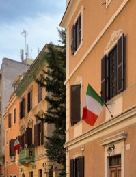 """Tuesday, May 5, 2020 – Italians are generally not patriotic in the same way as Americans and never hang flags outside their homes, but a sense of national solidarity was strong during the lockdown. Many people hung the """"Tricolore"""" from their windows or balconies, including these two houses on the block I live on. Rome, Italy. Lauren Phillips"""