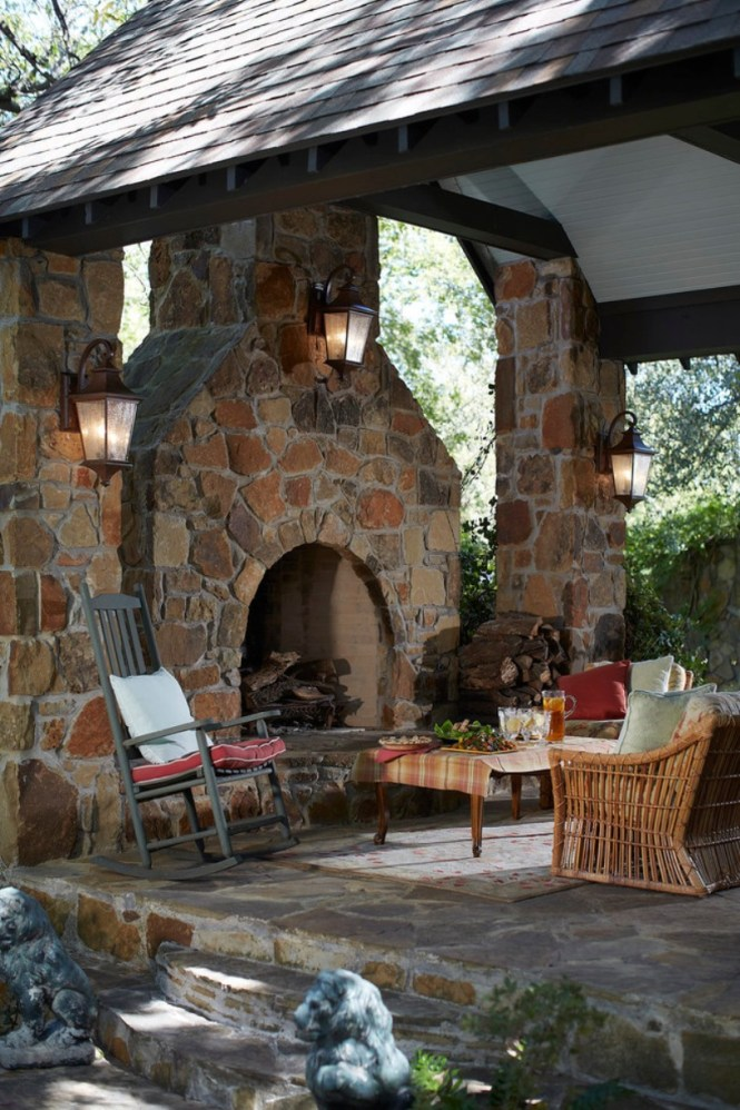Rustic Patio With A Stone Fireplace And Pillars