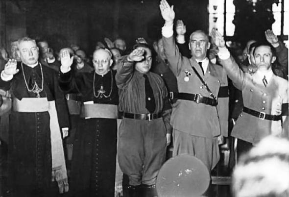 Together with interior minister Wilhelm Frick (second from the right) and propaganda minister Joseph Goebbels (far right), Catholic bishops Franz Rudolf Bornewasser (Bishop of Trier) and Lugwig Sebastian (Bishop of Speyer) raise their hands in the Nazi salute at an official ceremony in Saarbrucken City Hall marking the reincorporation of the Saarland into the German Reich.