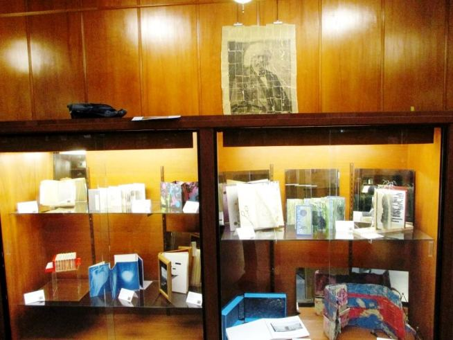 """(bottom shelf, far left) """"The Accordion Book of Short Stories;"""" (on wall)"""