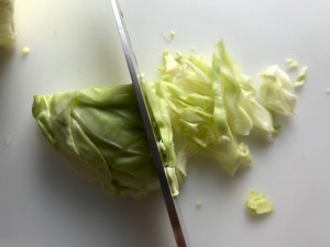 Knife slicing cabbage thin for Asian Coleslaw. It has cabbage, carrots, scallions, and sesame seeds in a creamy dressing with mayonnaise. vinegar, soy sauce, and Sesame Oil. It really is a sidekick that can go with anything!
