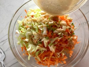 Pouring asian Dressing over carrots and cabbage in bowl for Asian Coleslaw. It has cabbage, carrots, scallions, and sesame seeds in a creamy dressing with mayonnaise. vinegar, soy sauce, and Sesame Oil. It really is a sidekick that can go with anything!