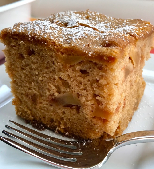Slice of the Best Apple Cinnamon Cake on a plate with a fork. When you bake this cake, the entire house fills with the amazing aroma of cinnamon and apples. And then when you eat it, every bite gives you sweet cinnamon spice with a beautifully spongy texture and a sweet and tart pop from the apples.
