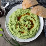 Edamame Dip with Gorgonzola and Harissa Oil drizzled on top on a plate with bread. It's creamy, savory, nutty, and utterly delicious!